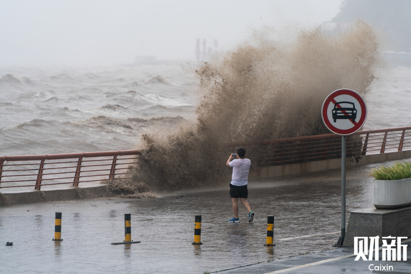 A man takes photos of the stormy waters in Zhoushan, East China's Zhejiang province, during a typhoon on July 25. Photo: Liang Yingfei/Caixin