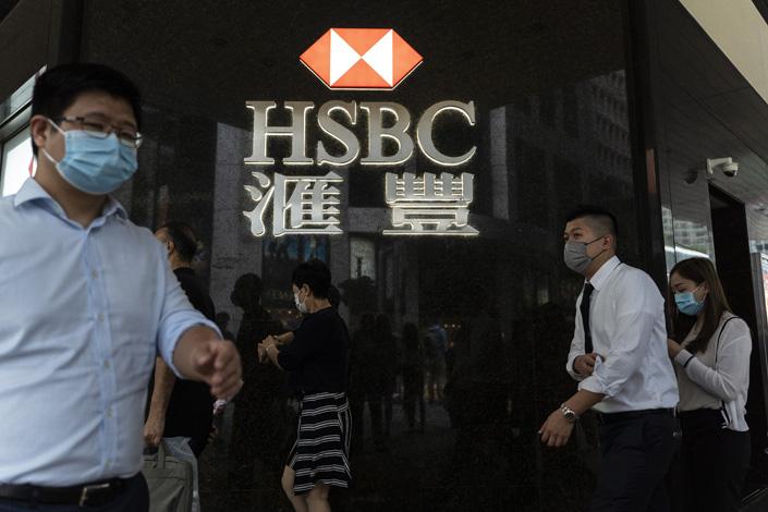 Pedestrians wearing protective masks walk past a HSBC branch in Hong Kong, in September 2020. Photo: VCG