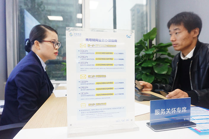 A customer inquires about transferring his phone number from one carrier to another at a China Mobile office in Hangzhou, East China's Zhejiang province, in November 2019. Photo: VCG