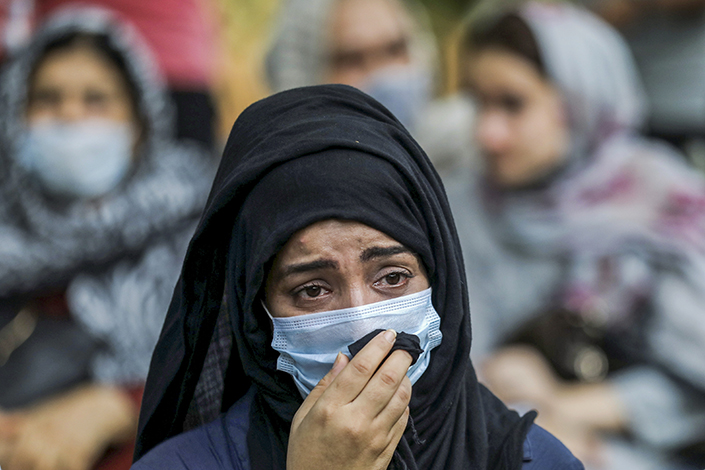 A woman cries at a meeting that urges international society to help Afghan women on Wednesday.