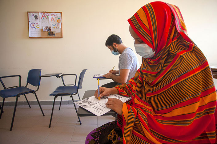 Two refugees from Afghanistan take Italian lessons in Molfetta, Italy, on Friday. Photo: VCG