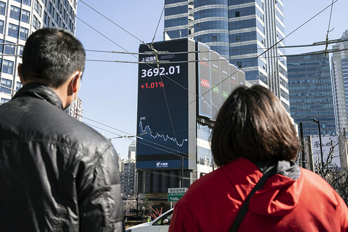 Pedestrians walk past a screen displaying the SSE Composite Index in Shanghai on Feb. 18. Photo: Bloomberg
