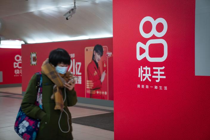 A passenger wearing a mask walks past Kuaishou Technology advertisements at a subway station in Beijing, China, on Wednesday, Feb. 3. Photo: Bloomberg