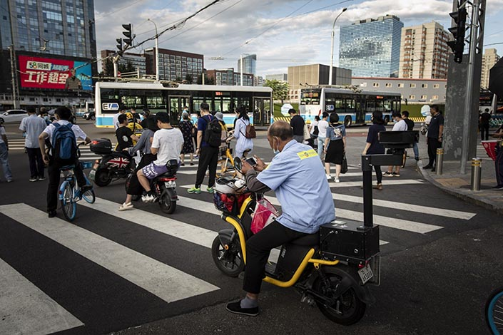 Commuters wait at a traffic intersection in Beijing, China, on Wednesday, Aug. 25, 2021. Photo: Bloomberg