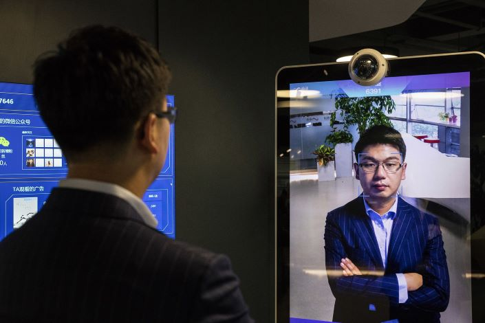 SenseTime CEO Xu Li gets identified by the company's facial recognition system while posing for a photo at the company's showroom in Beijing in June 2018. Photo: Bloomberg