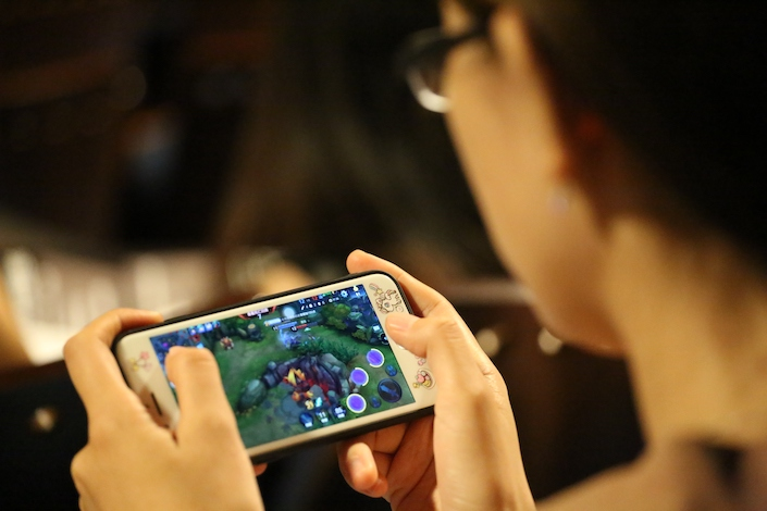 A gamer playing Tencent's Honor of Kings on mobile phone.
