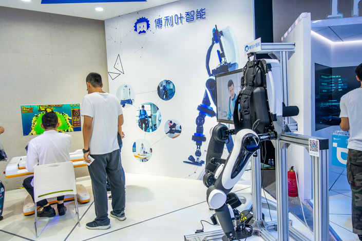 Workers demonstrate how to operate a Fourier exoskeleton robot at the 2018 World Artificial Intelligence Conference in Shanghai in September 2018. Photo: VCG