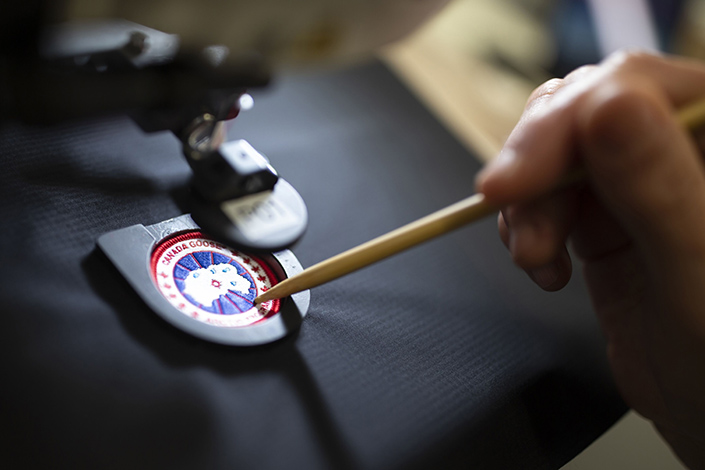 An employee arranges a logo patch in a sewing machine at the new Canada Goose Inc. manufacturing facility in Montreal, Quebec, Canada, in April 2019. Photo: Bloomberg