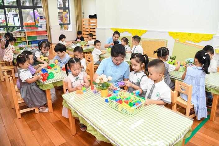 A teacher helps kindergarten pupils play with toys in a kindergarten in Haikou, South China's Hainan province, on Sept. 1. Photo: VCG