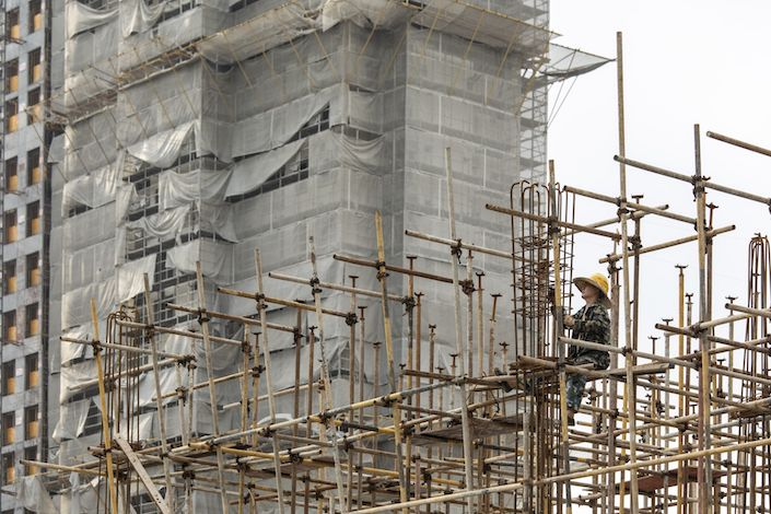 A worker labors on scaffolding at an under construction residential housing development in Shanghai