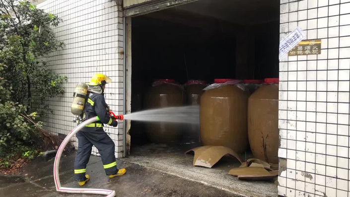 A firefighter hoses down the flammable