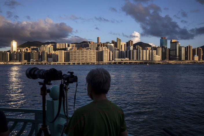 A photographer waits for the super blood moon to rise over the city's skyline in Hong Kong