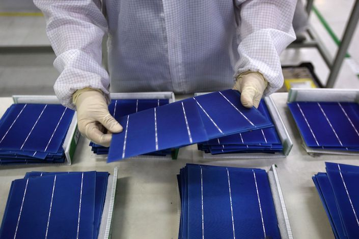An employee performs a final inspection on solar cells on the production line at the Trina Solar Ltd. factory in Changzhou