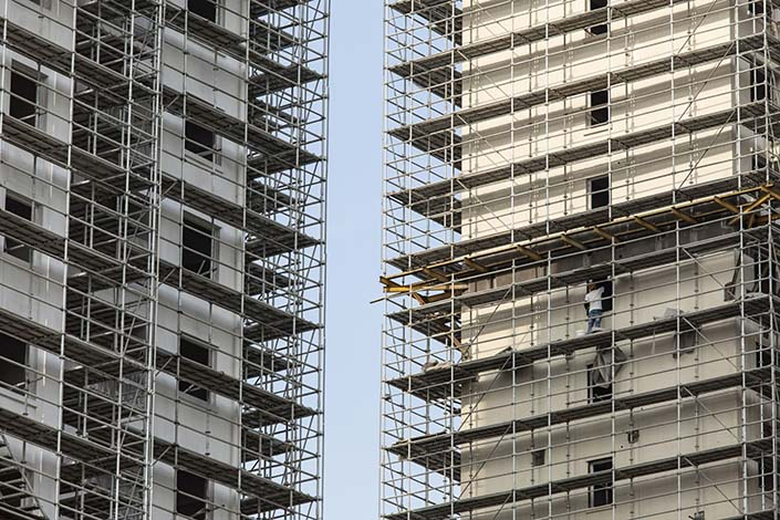 A construction worker labors on the scaffolding of a building at an under construction residential housing development in Shanghai on July 29. Photo: Bloomberg