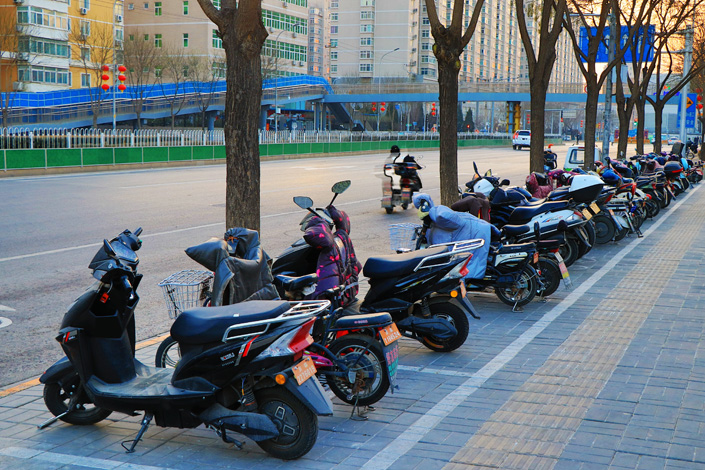 Electric bicycles are parked in a row on a street in Beijing on Jan. 30. Photo: VCG