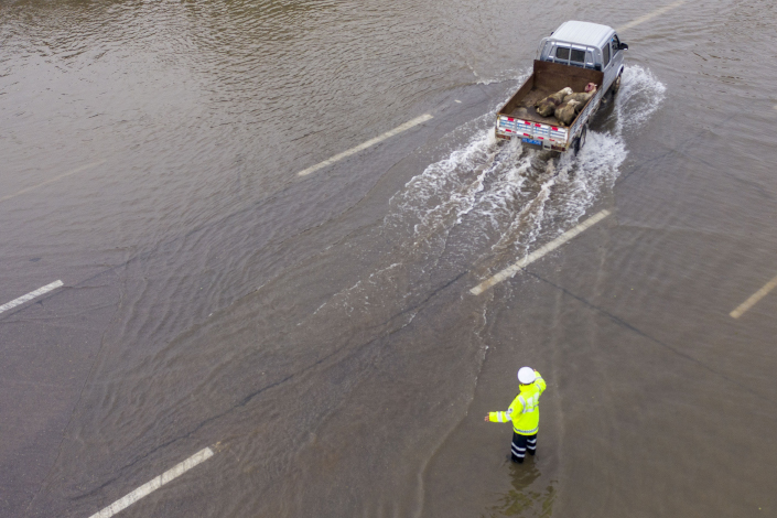 A police officer directs traffic after heavy rain in Jishan county, North China's Shanxi province, on Thursday. Photo: VCG