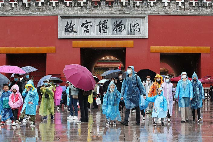 Tourists come out of the Forbidden City, a popular tourist attraction in Beijing, in the rain on Wednesday. Photo: VCG