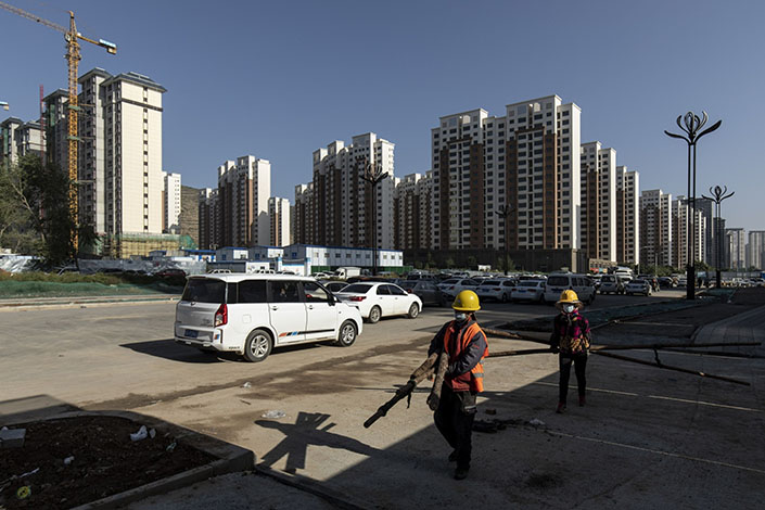 Workers carry wooden poles near apartment blocks under construction in the Nanchuan area of Xining, Qinghai province, on Sept. 28.Photo: Bloomberg
