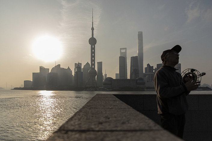 A man flies a kite on the Bund against the backdrop of the Lujiazui Financial District in Shanghai on April 10. Photo: Bloomberg