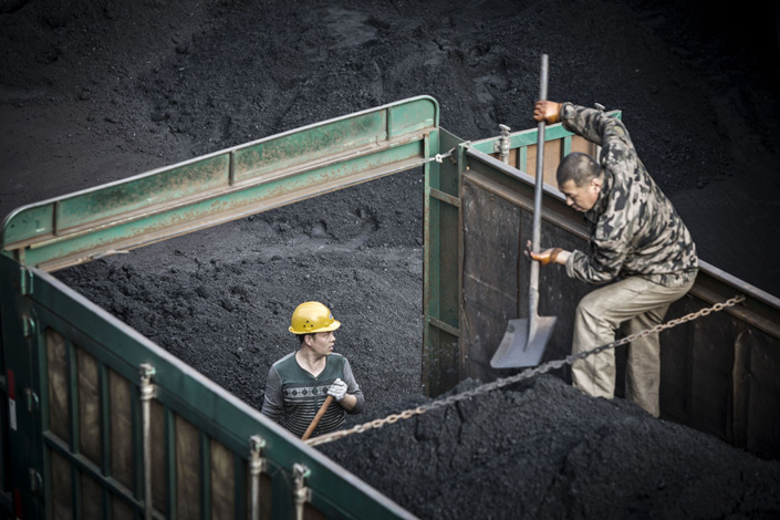 Employees unload coal from a truck at a mine and processing facility in Liulin, North China's Shanxi province, in May 2016.  Photo: Bloomberg