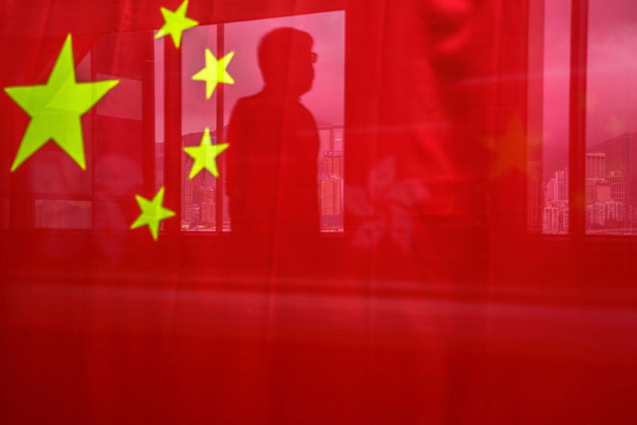 A pedestrian is seen through a Chinese flag ahead of the anniversary of Hong Kong's return to China on June 30. Photo: Bloomberg