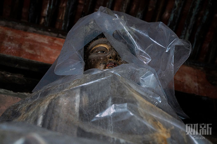 Plastic covers a Buddha statue at Longxing Temple in Xinjiang county, North China's Shanxi province. The statue was wrapped up to prevent damage from water leakage. Photo: Liang Yingfei/Caixin