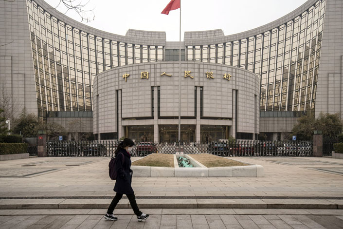 A pedestrian walks past the People's Bank of China headquarters in Beijing on March 4.  Photo: Bloomberg